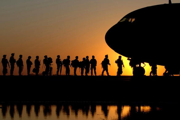 The sun sets behind a C-17 Globemaster III as Soldiers wait in line to board the aircraft taking them back to the United States Nov. 17 at Joint Base Balad, Iraq. C-17s can carry payloads up to 169,000 pounds and can land on small airfields. The C-17 is deployed from the 437th Airlift Wing at Charleston Air Force Base, S.C. (U.S. Air Force photo/Tech. Sgt. Erik Gudmundson)